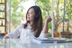 美好的亚洲妇女关闭她的眼睛和喜欢听到与耳机的音乐在充满感觉的咖啡馆放松 免版税库存照片