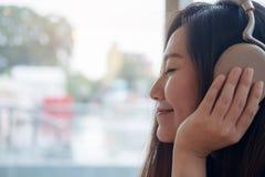 美好的亚洲妇女关闭她的眼睛和喜欢听到与耳机的音乐在充满感觉的现代咖啡馆放松和愉快 免版税库存图片