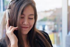 美好的亚洲妇女关闭她的眼睛和喜欢听到与耳机的音乐在充满感觉的现代咖啡馆放松和愉快 图库摄影