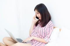美好的亚洲少妇设置画象在床上的使用便携式计算机和在卧室的谈话巧妙的电话休闲的和放松 免版税库存照片