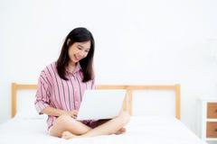 美好的亚洲少妇设置画象在床上的使用在卧室的便携式计算机休闲的和放松 免版税图库摄影