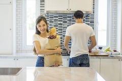 美好的亚洲年轻夫妇爱恋微笑看对cookin 免版税库存图片