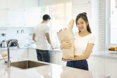 美好的亚洲年轻夫妇看对烹调在厨房里 免版税图库摄影