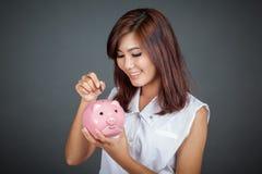 美好的亚洲女孩微笑投入硬币变粉红色猪钱箱 免版税库存图片