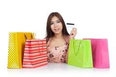 美好的亚洲妇女展示与购物袋的一张信用卡 免版税图库摄影