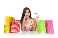 美好的亚洲妇女展示与购物袋的一张信用卡 库存图片