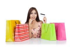 美好的亚洲妇女展示与购物袋的一张信用卡 免版税库存图片