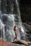 美好的亭亭玉立的健身式样摆在性感在瀑布前面 免版税图库摄影