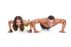 美好的做俯卧撑的健身年轻运动的夫妇 免版税图库摄影