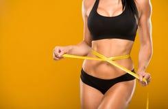 美好的健身模型测量在黄色的腰部 免版税图库摄影