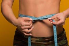 美好的健身模型测量在黄色的腰部 库存照片