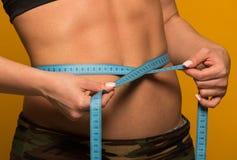 美好的健身模型测量在黄色的腰部 库存图片