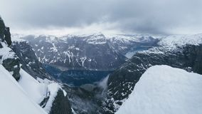 美好的冬天山全景在挪威,方式toTrolltunga的 在高岩石之间的惊人的蓝色湖在雪下 库存照片
