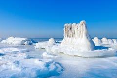 美好的冬天海景 冰土坎和用冰盖的一个老码头的遗骸 免版税库存图片