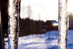 美好的冰柱在太阳发光反对蓝天 与垂悬从房子屋顶的冰冰柱的春天风景  春天投下冰柱 库存图片