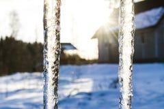 美好的冰柱在太阳发光反对蓝天 与垂悬从房子屋顶的冰冰柱的春天风景  春天投下冰柱 库存照片