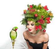 美好的创造性的Xmas构成和发型室内射击 秀丽有绿色鹦鹉的时装模特儿女孩 免版税图库摄影