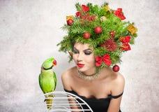 美好的创造性的Xmas构成和发型室内射击 秀丽有绿色鹦鹉的时装模特儿女孩 免版税库存图片