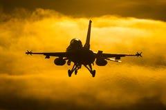 美好的喷气式歼击机日落着陆 免版税库存照片