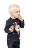 美好的圣诞节例证魔术雪花向量妇女 吃在白色的逗人喜爱的男孩一个曲奇饼 库存图片