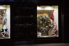 美好的圣诞节显示 在一个窗口,假日花圈,圣诞老人` s驯鹿玩偶的圣诞老人玩偶 免版税库存图片
