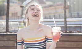 美好的在一条城市街道上的年轻人微笑白肤金发的女孩在一个晴天喝与冰的刷新的水果鸡尾酒 免版税图库摄影