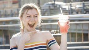 美好的在一条城市街道上的年轻人微笑白肤金发的女孩在一个晴天喝与冰的刷新的水果鸡尾酒 免版税库存照片