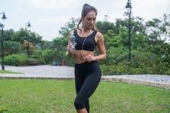 美好的在站立在草在城市公园和听的黑运动服的健身女性模型全长射击  免版税库存照片