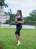 美好的在站立在草在城市公园和听的黑运动服的健身女性模型全长射击  免版税库存图片