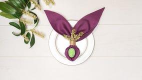 美好的复活节桌设置用鸡蛋,紫色餐巾复活节兔,春天绿色在白色木背景的树枝 免版税图库摄影