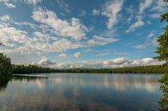 美好的夏天横向 从海岸的看法向一个美丽如画的森林湖在蓝色多云天空下 免版税库存图片