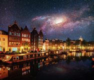 美好的夜在阿姆斯特丹 大厦和小船的夜照明在水附近在运河 美国航空航天局礼貌  免版税库存照片