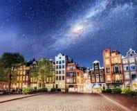 美好的夜在阿姆斯特丹 大厦和小船的夜照明在水附近在运河 免版税库存图片