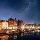 美好的夜在阿姆斯特丹 大厦和小船的夜照明在水附近在运河 免版税库存照片