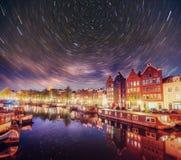 美好的夜在阿姆斯特丹 大厦和小船的夜照明在水附近在运河 图库摄影