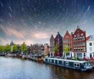 美好的夜在阿姆斯特丹 大厦和小船的夜照明在水附近在运河 库存图片