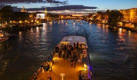 美好的夜巴黎,闪耀的埃菲尔铁塔、桥梁艺术桥在河塞纳河和旅游小船 ?? 免版税库存图片