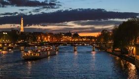 美好的夜巴黎,闪耀的埃菲尔铁塔、桥梁艺术桥在河塞纳河和旅游小船 ?? 免版税图库摄影