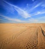 美好的天空视图和沙丘与轮子轨道 库存图片