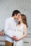 美好的夫妇、怀孕的拥抱充满爱的少妇和人,在钢琴背景 免版税库存图片