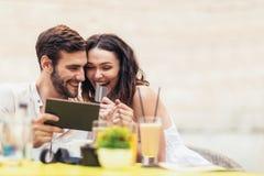 美好的夫妇喝咖啡在日期,使用数字式片剂和信用卡 免版税库存照片