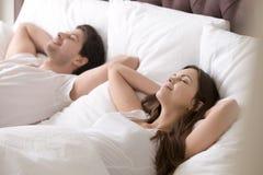 美好的夫妇在与眼睛的床上关闭了,休息和微笑 免版税库存照片