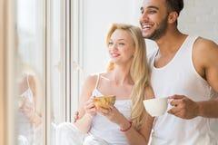 年轻美好的夫妇在大窗口、饮料早晨咖啡杯、愉快的微笑西班牙男人和妇女附近站立 免版税图库摄影