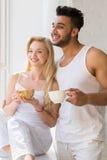 年轻美好的夫妇在大窗口,饮料早晨咖啡杯,愉快的微笑西班牙人妇女附近站立 库存图片