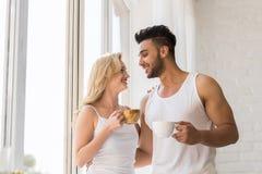 年轻美好的夫妇在大窗口,饮料早晨咖啡杯,愉快的微笑西班牙人妇女附近站立 免版税图库摄影