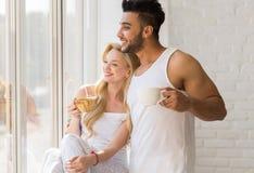 年轻美好的夫妇在大窗口,饮料早晨咖啡杯,愉快的微笑西班牙人妇女附近站立 库存照片