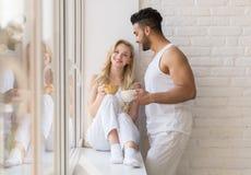 年轻美好的夫妇在大窗口,饮料早晨咖啡杯,愉快的微笑西班牙人妇女附近站立 免版税库存照片