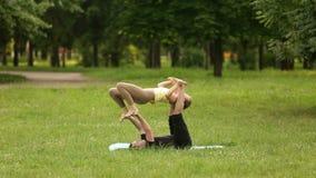 美好的夫妇实践的acro瑜伽 年轻瑜伽辅导员在绿草的一个城市公园实践 两成功 影视素材