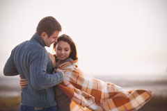 年轻美好的夫妇特写镜头在毯子下的在冷的天ne 图库摄影