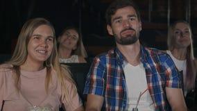 美好的夫妇笑和耳语对她的人在影片期间在电影院 免版税库存图片